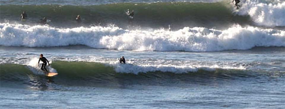 Surfers riding waves at Campus Point